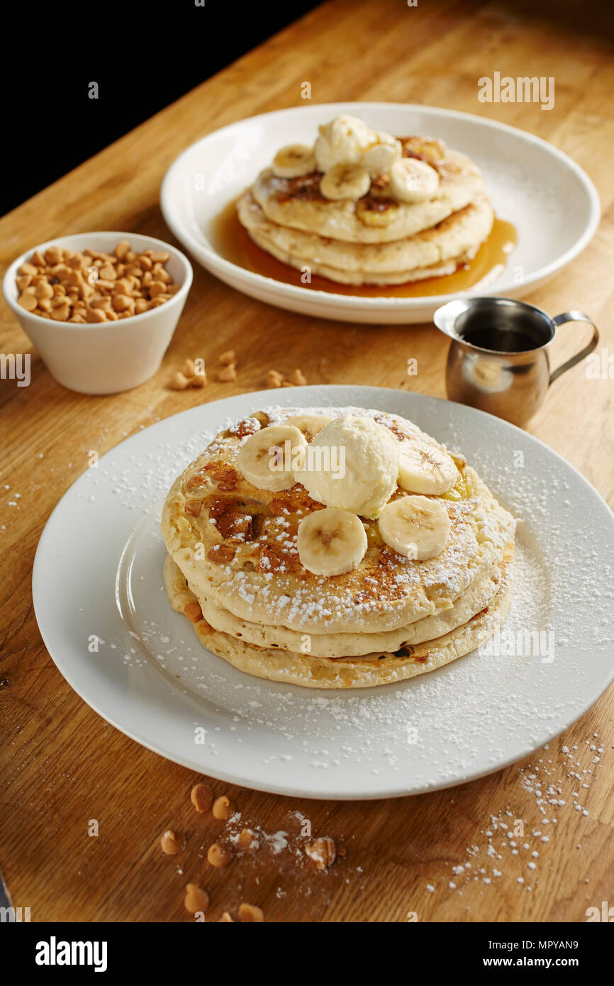 Close-up of pancakes served with banana slices in plate on table - Stock Image