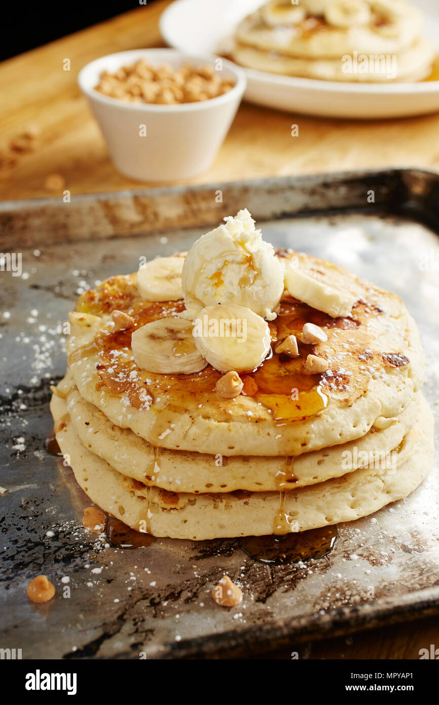 Close-up of pancakes with banana slices and syrup in tray on table - Stock Image