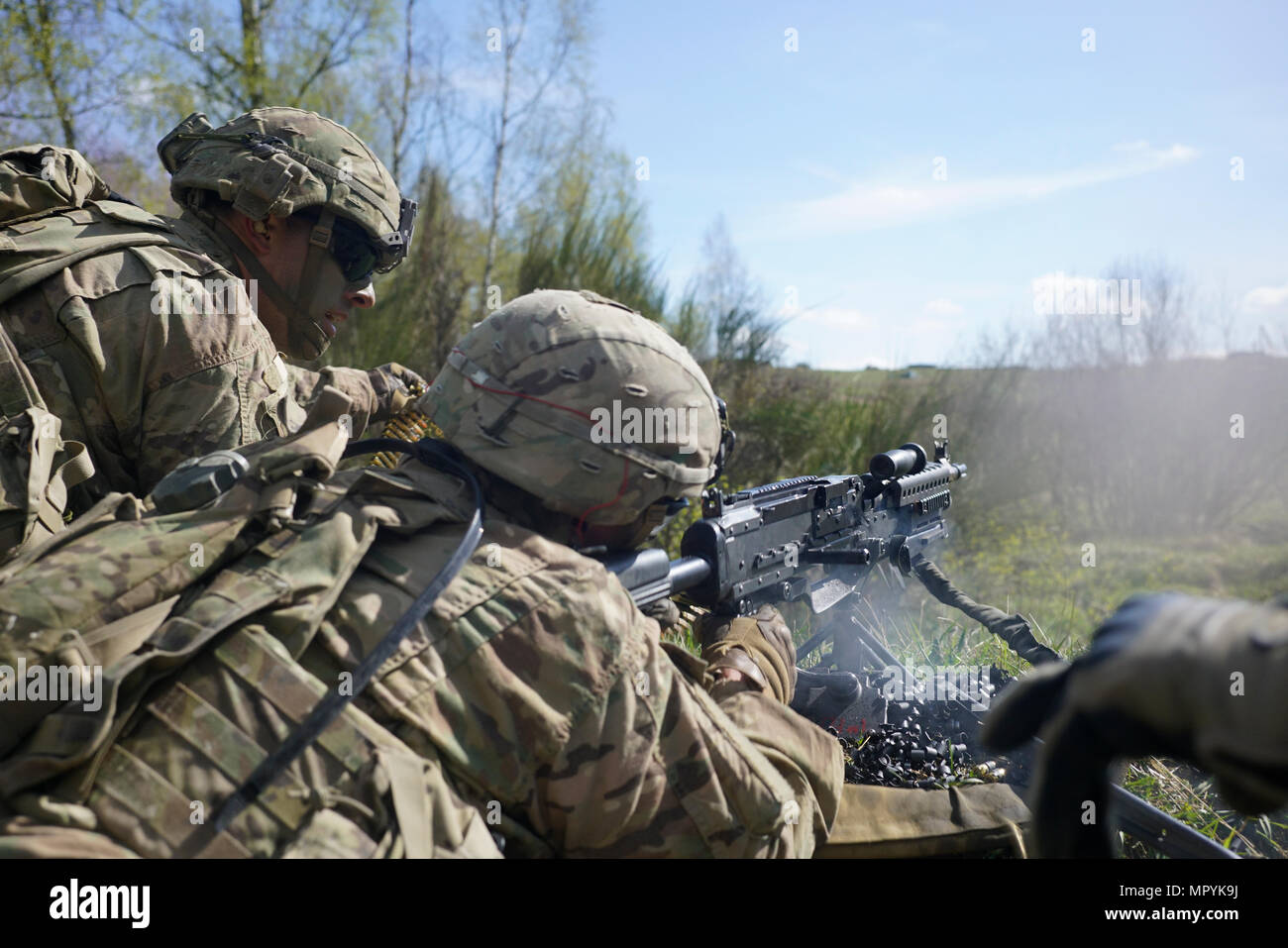 A U.S. Soldier of Comanche Troop, 4th Squadron, 10th Cavalry Regiment, 3rd Armored Brigade Combat Team, 4th Infantry Division provides suppressive fire with an M240 while conducting a live fire operation during Exercise Combined Resolve VIII at the Grafenwoehr Training Area, Germany April 24, 2017. Exercise Combined Resolve VIII is a multinational exercise designed to train the Army's Regionally Allocated Forces to the U.S. European Command. Combined Resolve VIII will include more than 3,400 participants from 10 nations. The goal of the exercise is to prepare forces in Europe to operate togeth - Stock Image