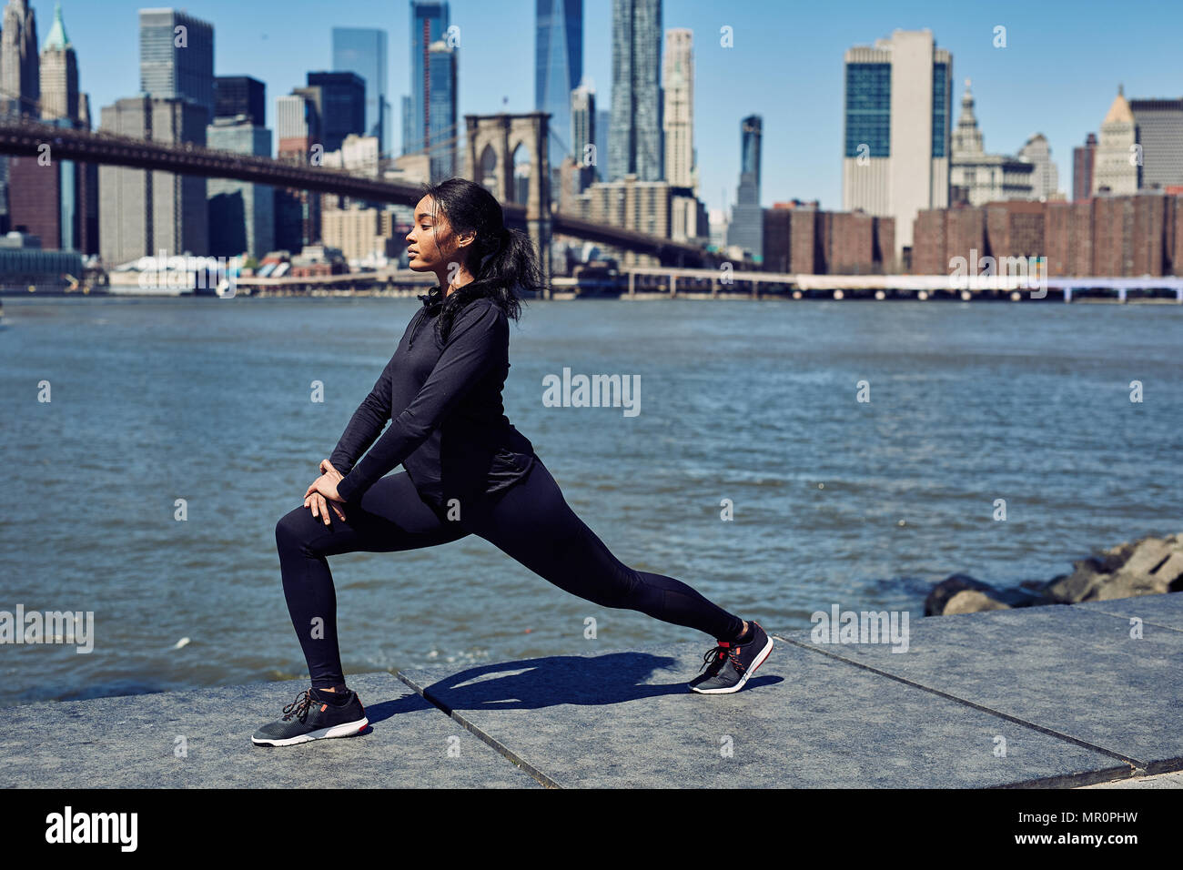 Black Woman Stretches Before Running in New York City - Stock Image