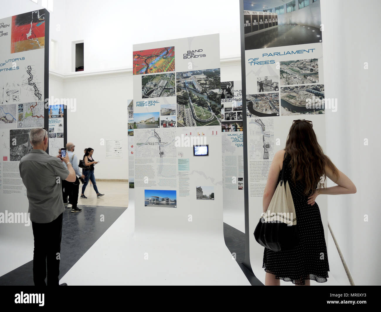 24 May 2018, Italy, Venice: Visitors peruse the exhibition 'Unbuilding Walls' by architecture group Graft at the German pavilion of the 16th International Architecture Exhibition. The Biennale runs from 26 May to 25 November 2018. Photo: Lena Klimkeit/dpa - Stock Image