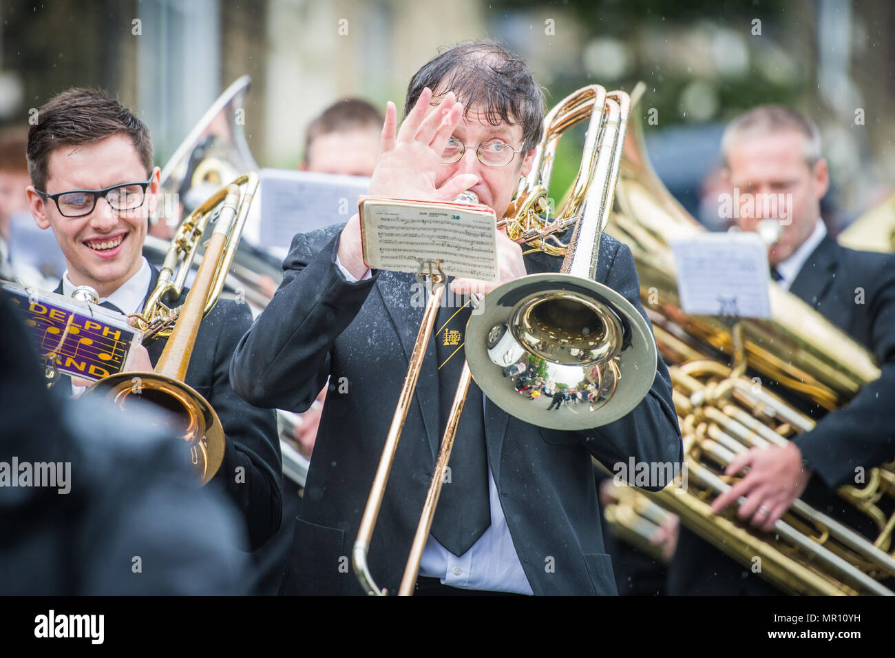 Delph, UK. 25th May 2018. A member of a brass band plays as they walk along the procession during the annual 'Whit Walks' through the village of Delph in the district of Saddleworth, Greater Manchester. Credit: Matthew Wilkinson/Alamy Live News Stock Photo