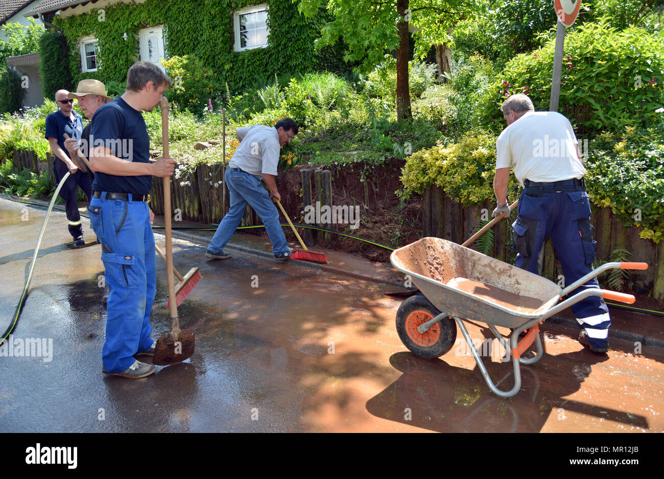 25 May 2018, Germany, Trassem: Residents and members of the Saarburg volunteer fire department clearing up. Heavy rain caused a landslide in Trassem in western Germany, which damaged several properties. Photo: Harald Tittel/dpa - Stock Image