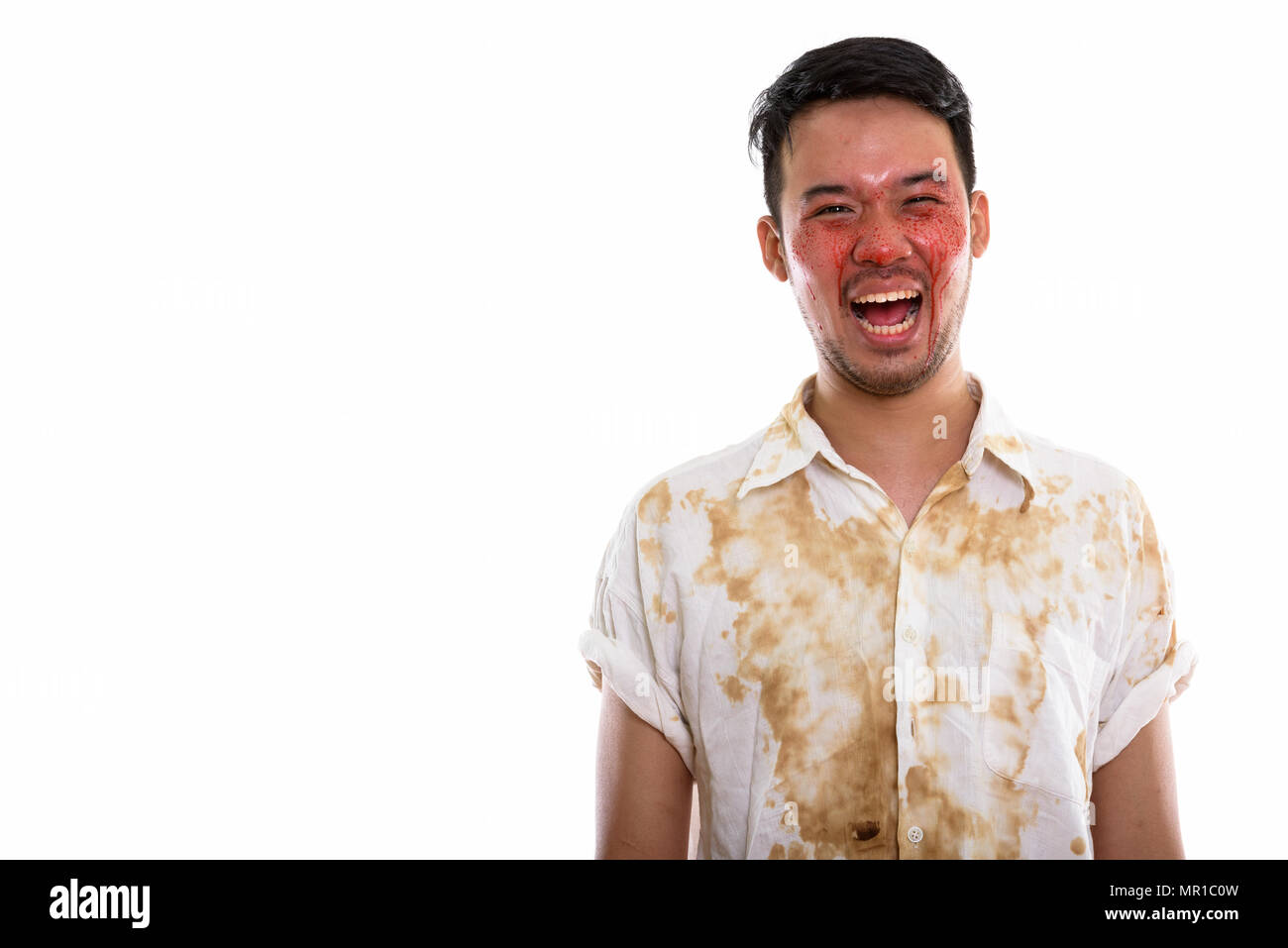 Studio shot of young happy crazy Asian man smiling and laughing  - Stock Image