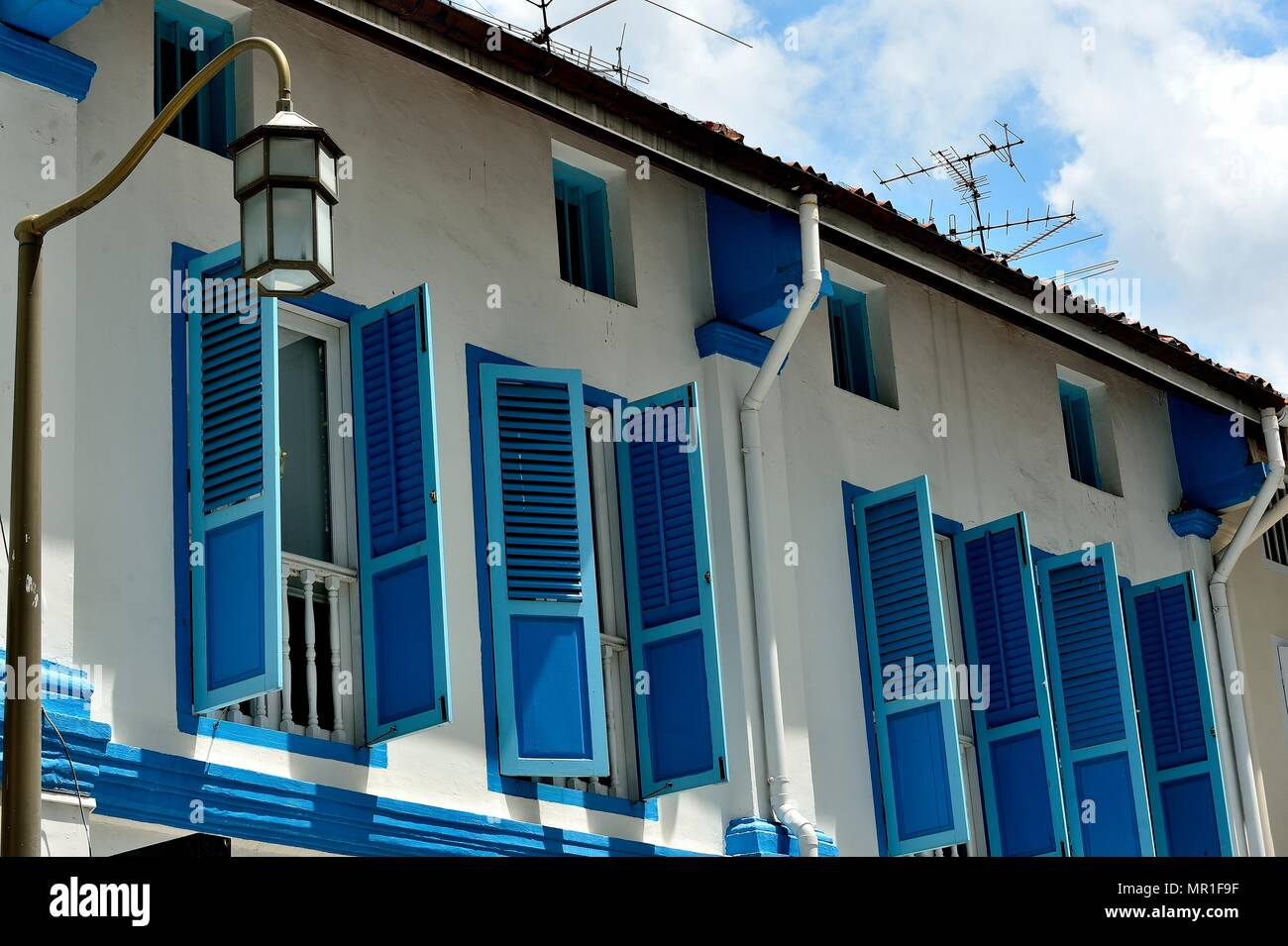 Vintage windows with antique blue wooden shutters on the exterior of a row of heritage Peranakan or Straits Chinese shophouses in historic Chinatown - Stock Image
