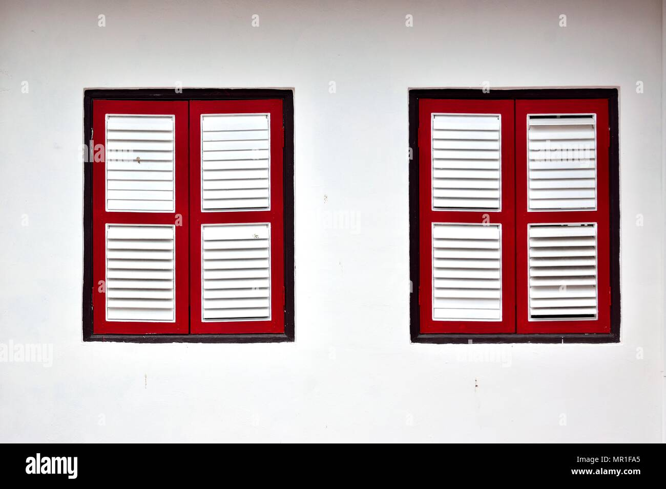 Front view of vintage wooden shuttered windows on the white exterior of an old Singapore shophouse in historic Chinatown - Stock Image
