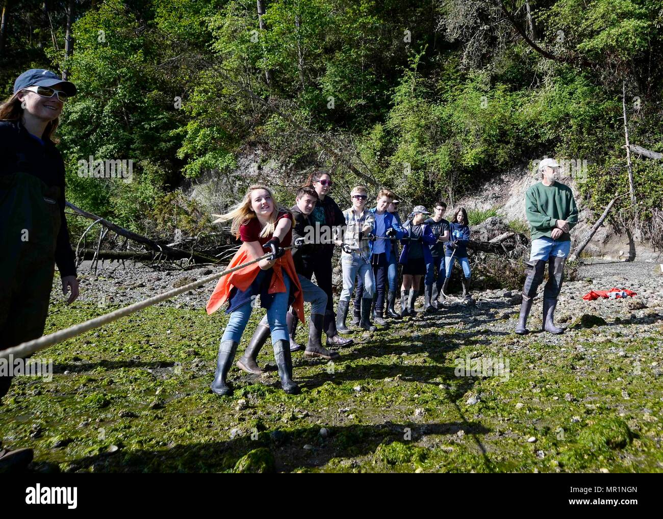 170428-N-VH385-046 INDIAN ISLAND, Wash., (April 28, 2017) – Students from Blue Heron Middle School heave on line to pull in a seining-net during a community outreach beach seining with the United States Geological Survey (USGS) at Naval Magazine Indian Island. This is the third year the USGS has teamed up with Blue Heron Middle School and Naval Magazine Indian Island to conduct beach seinings in preparation for the Kilsut Spit waterflow to be opened between Marrowstone and Indian Island. (U.S. Navy photo by Mass Communication Specialist 3rd Class Wyatt L. Anthony) - Stock Image