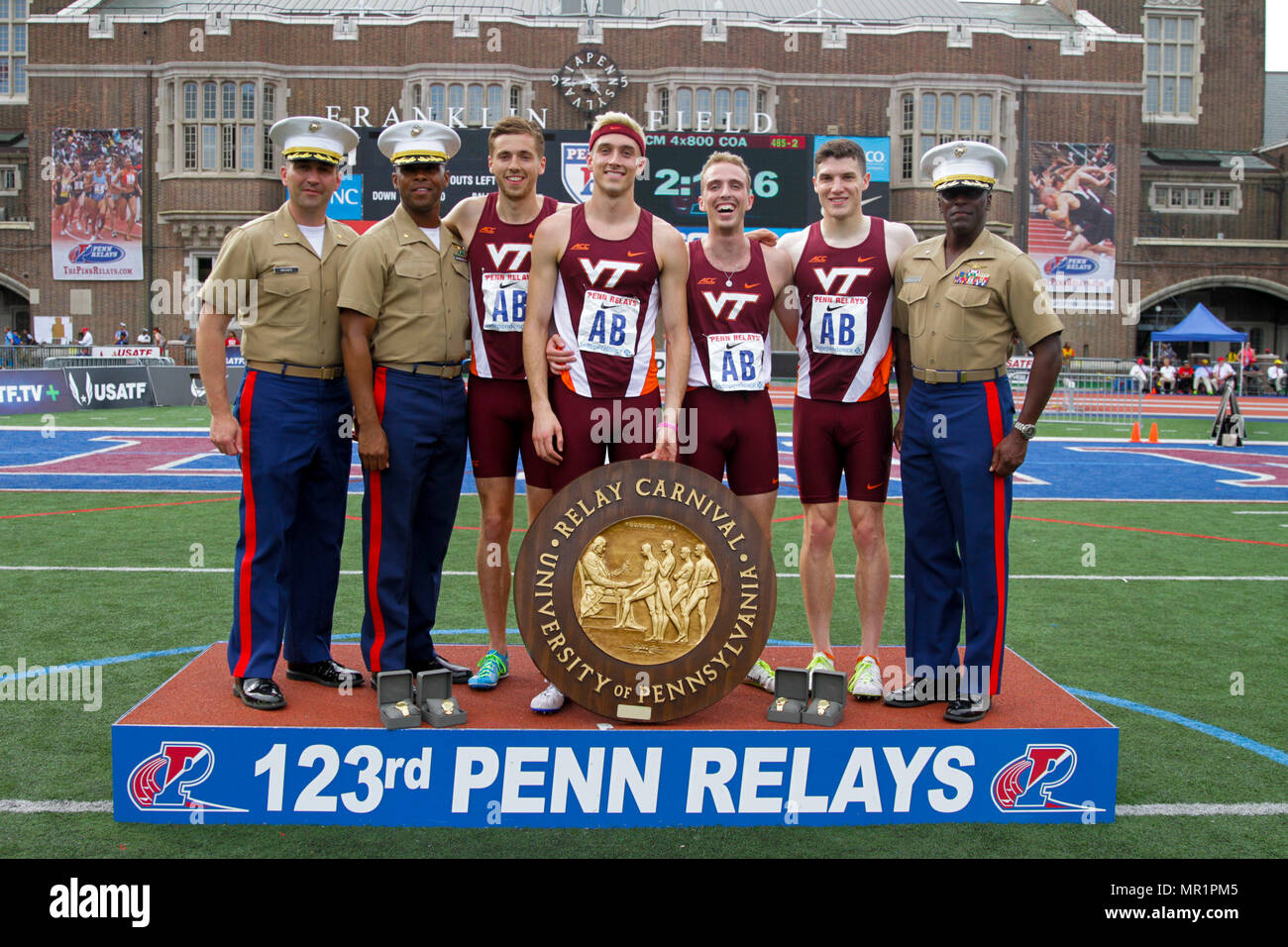 U.S. Marines present awards to the winners of the college men's 4x800 Champions of America Invitational during the 2017 Penn Relays in Philadelphia, April 29. This is the first time in the Penn Relay's 123-year history that Virginia Tech placed first in this event. (U.S. Marine Corps photo by Sgt. Brandon Thomas) - Stock Image