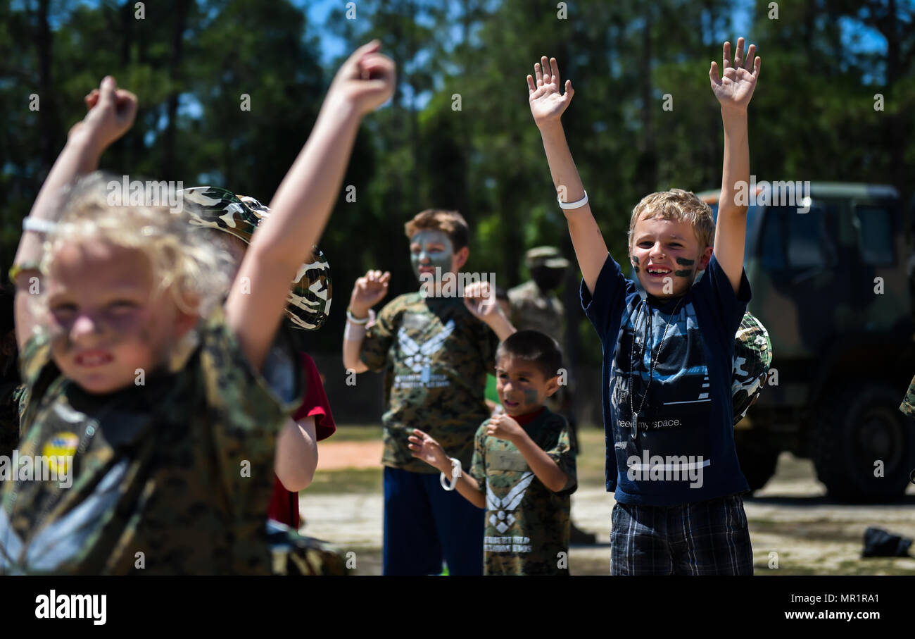 Military children participate in physical training at a deployed location during Operation Kids Understanding Deployment Operations at Hurlburt Field, Fla., April 22, 2017. At the deployed location, children visited a medical tent, shopped a field postal exchange and viewed a military working dog demonstration. (U.S. Air Force photo by Airman 1st Class Joseph Pick) - Stock Image