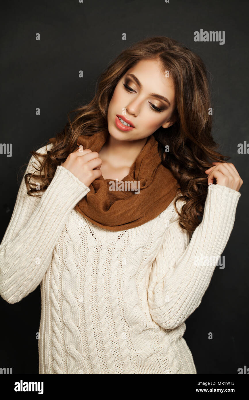 Beautiful Woman with Long Curly Hair and Makeup Wearing White Knitted Sweater and Cotton Scarf on Black Background Stock Photo