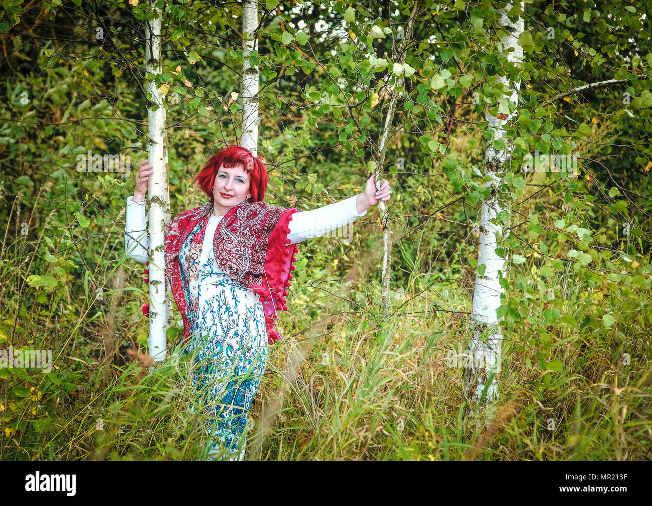 young beautiful girl with a kerchief on her shoulders near a birch tree in the forest - Stock Image
