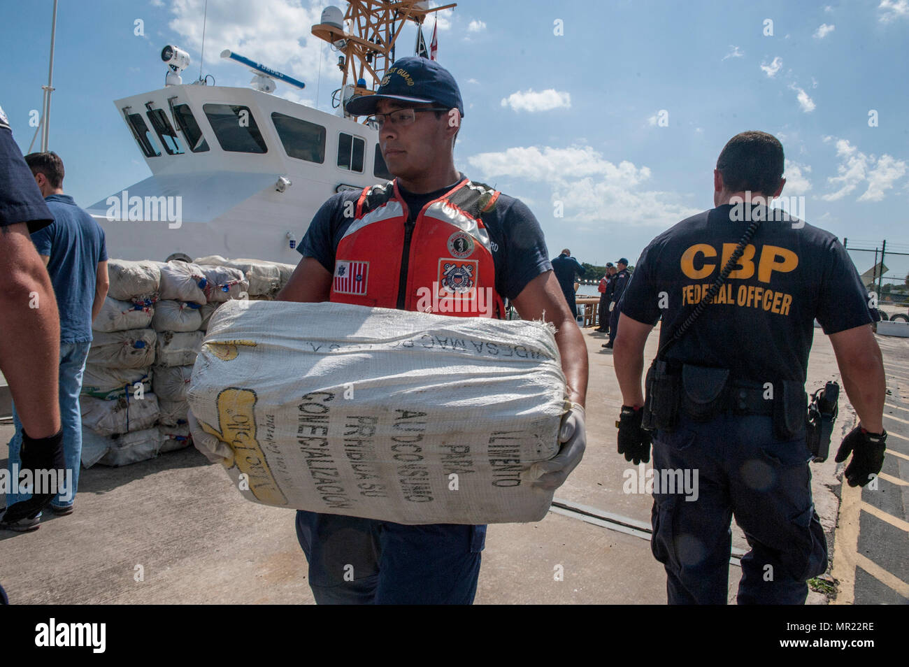 A crew member from Coast Guard Cutter Tarpon, an 87-foot Coast Patrol Boat homeported in St. Petersburg, Florida, and his crew offload 1,735 kilograms of cocaine, an estimated wholesale value of $56 million, Wednesday, May 3, 2017 at Coast Guard Sector St. Petersburg, Florida. The contraband was interdicted during four separate cases supporting Operation Martillo, a joint interagency and multi-national collaborative effort among 14 Western Hemisphere and European nations to stop the flow of illicit cargo by Transnational Criminal Organizations. (U.S. Coast Guard photo by Petty Officer 1st Clas - Stock Image
