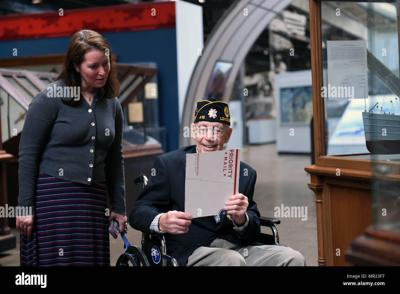 170502-N-FJ200-019  WASHINGTON (May 2, 2017) Thurman E. Scott Sr., a veteran of World War II and the Korean War, shows Jennifer Marland, curator at the National Museum of the U.S. Navy, a photograph of one of his brothers that served in the Navy during World War II.  Scott and four of his brothers served in the Navy while his fifth brother served in the U.S. Army Air Corps. (U.S. Navy photo by Mass Communication Specialist 1st Class Clifford L. H. Davis/Released) - Stock Image
