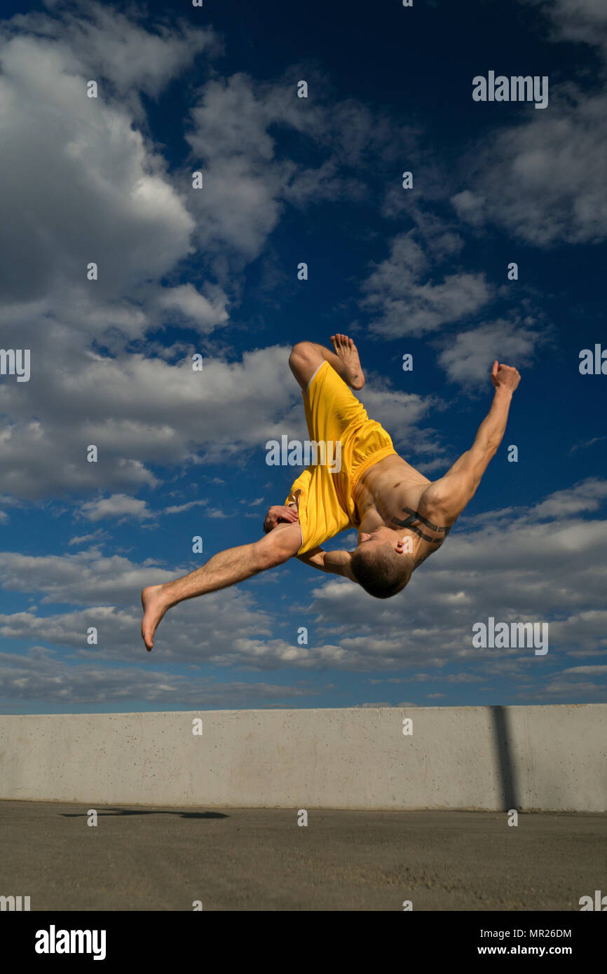 Tricking on street. Martial arts. Man does somersault ahead barefoot. Shooted from bottom foreshortening against sky. - Stock Image