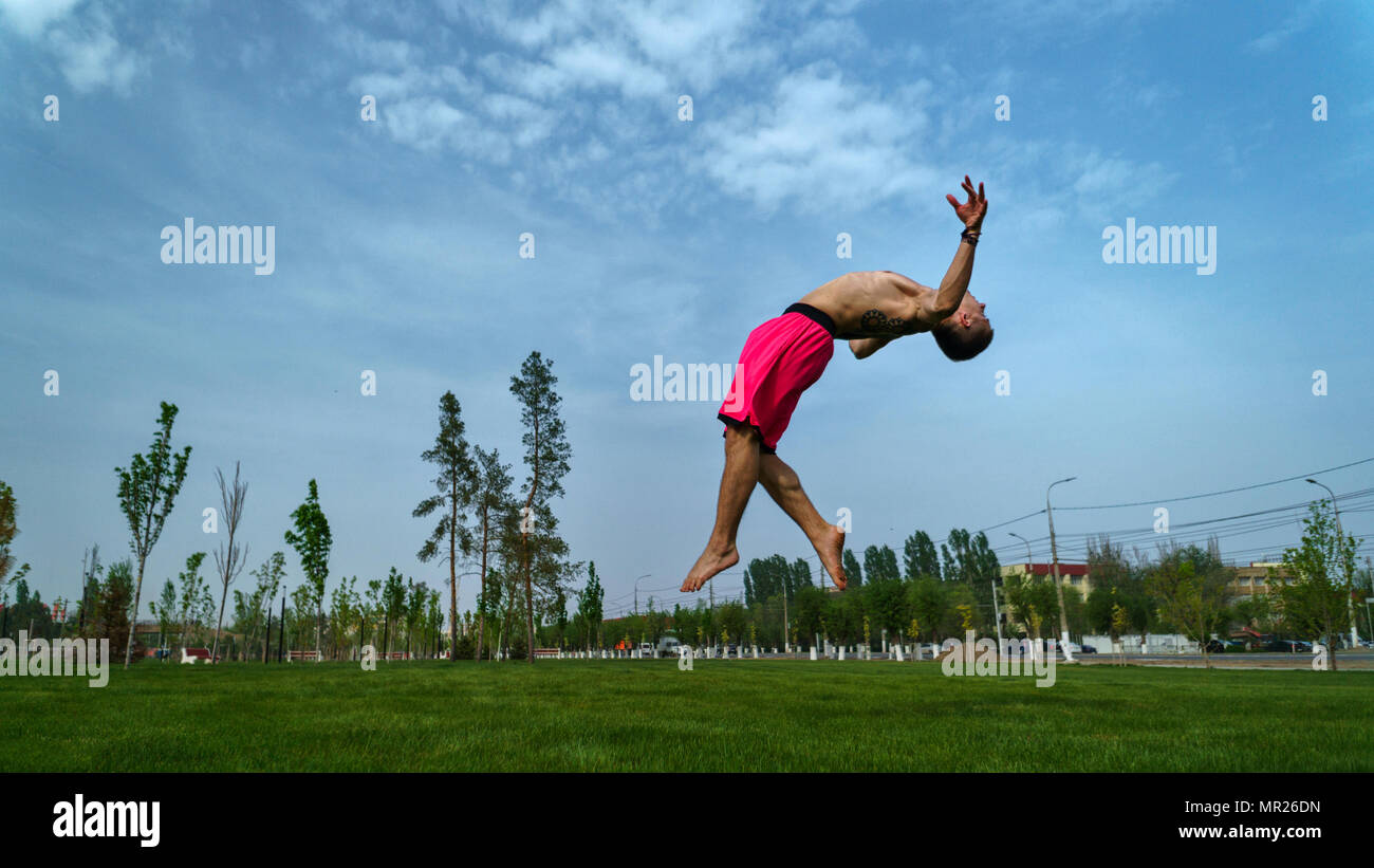Tricking on lawn in park. Man does back flip. Martial arts and parkour. Street workout. - Stock Image