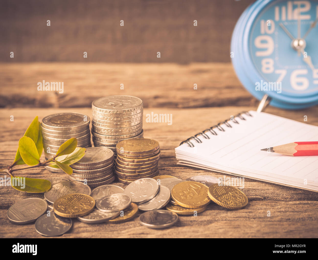Vintage baby tree with coins, red pencil, noot book and alarm clock on old wooden background. Business financce and saving money concpt. - Stock Image