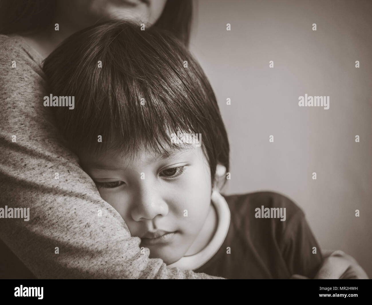 black and white sad boy being hugged by his mother at home
