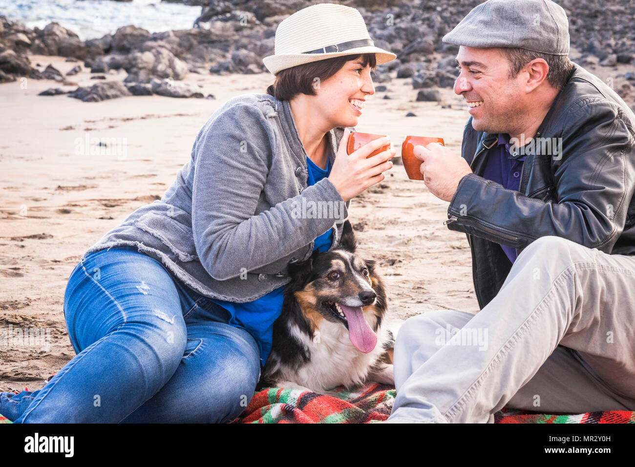 family with a border collie dog doing pic nic activity on the beach in vacation, summer lifestyle with friends concept. old style and vintage filter.  Stock Photo