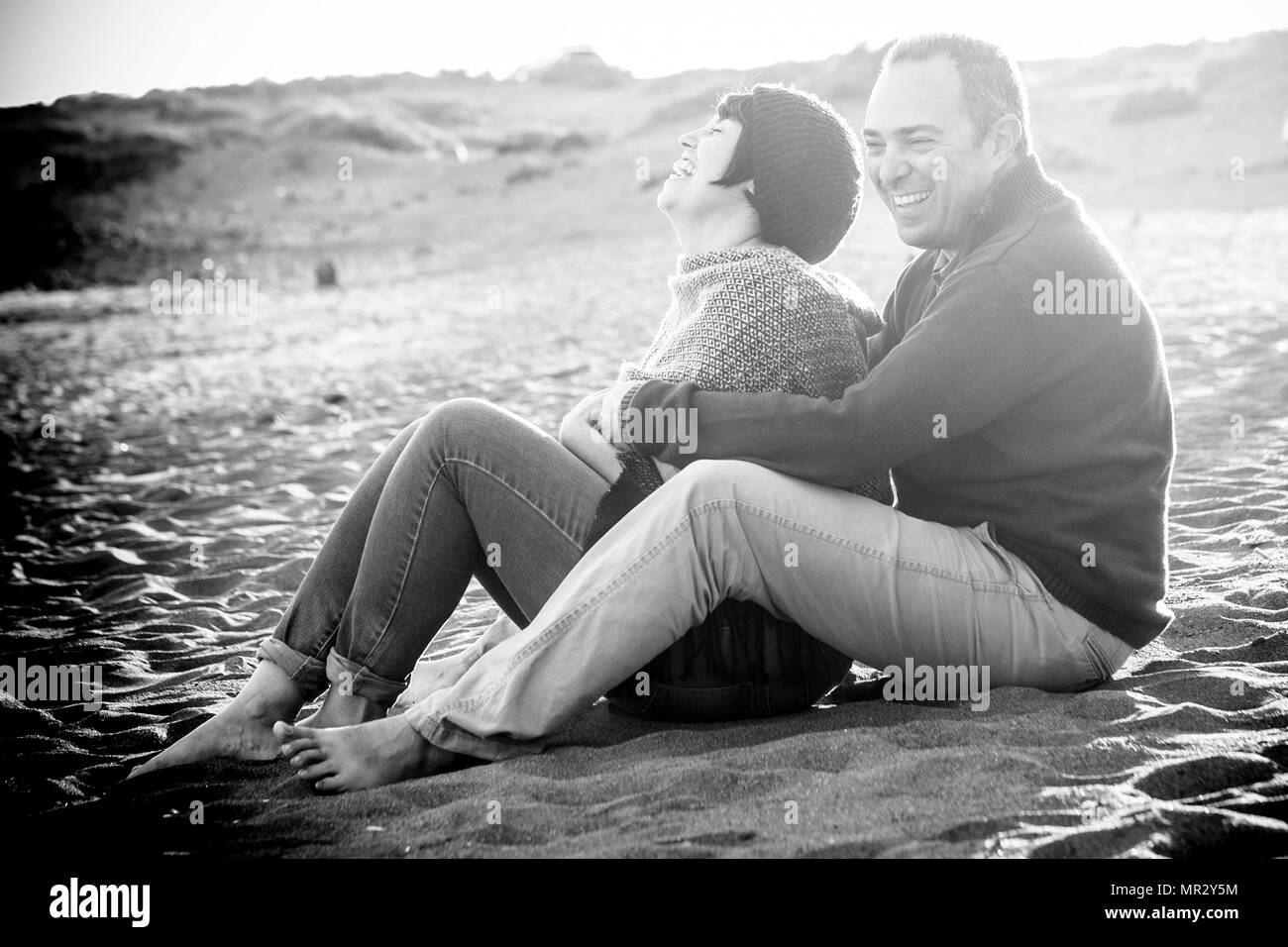 cute man and woman middle aged having fun in love at the beach outdoor. leisure activity and big smile and laugh for the lady. the man embrace her. ro - Stock Image