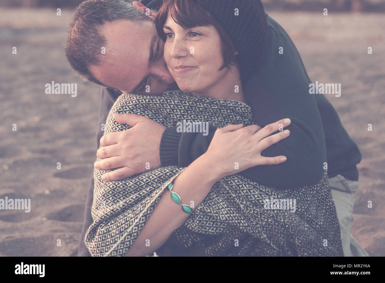 cute man and woman middle aged having fun in love at the beach outdoor. leisure activity and big hug for love concept and romantic scene the man embra - Stock Image