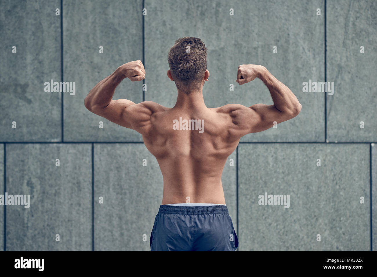 Young male bodybuilder posing with his back to the camera - Stock Image