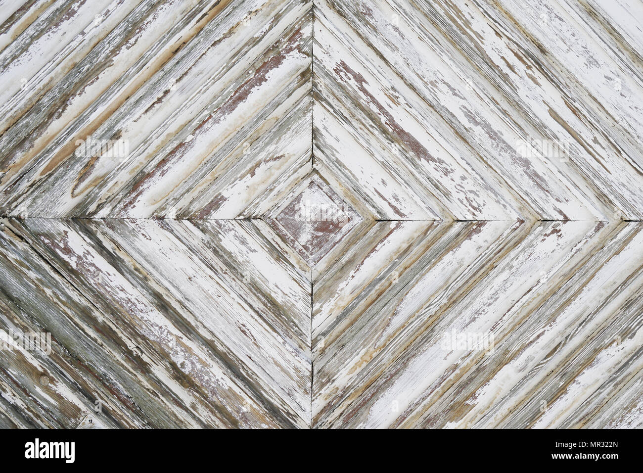 distressed wood paneling background texture pattern, detail of old weathered wooden door with white paint peeling off - Stock Image