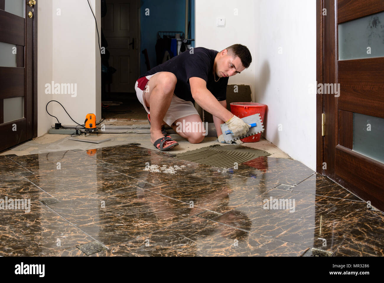 Laying Ceramic Tiles While Repairing In Room And Applying Glue To