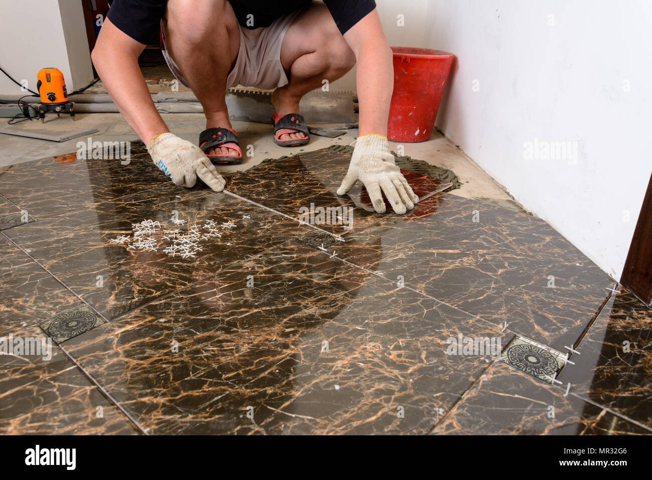 A Man Places A Ceramic Tile Under Pressure Over A Glue In Room Of