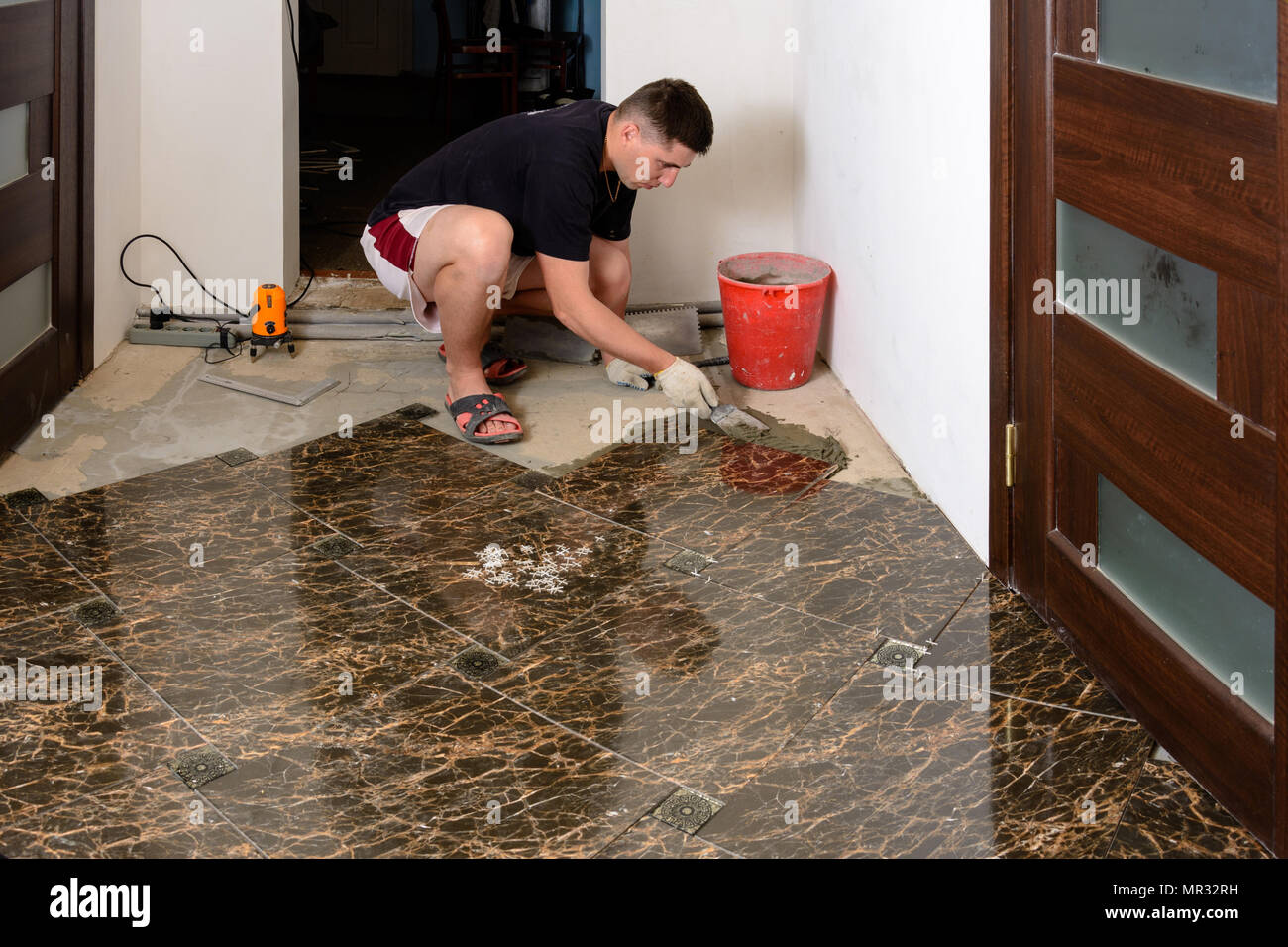 A Man Takes Extra Glue To Install A Ceramic Brown Tile In A Small