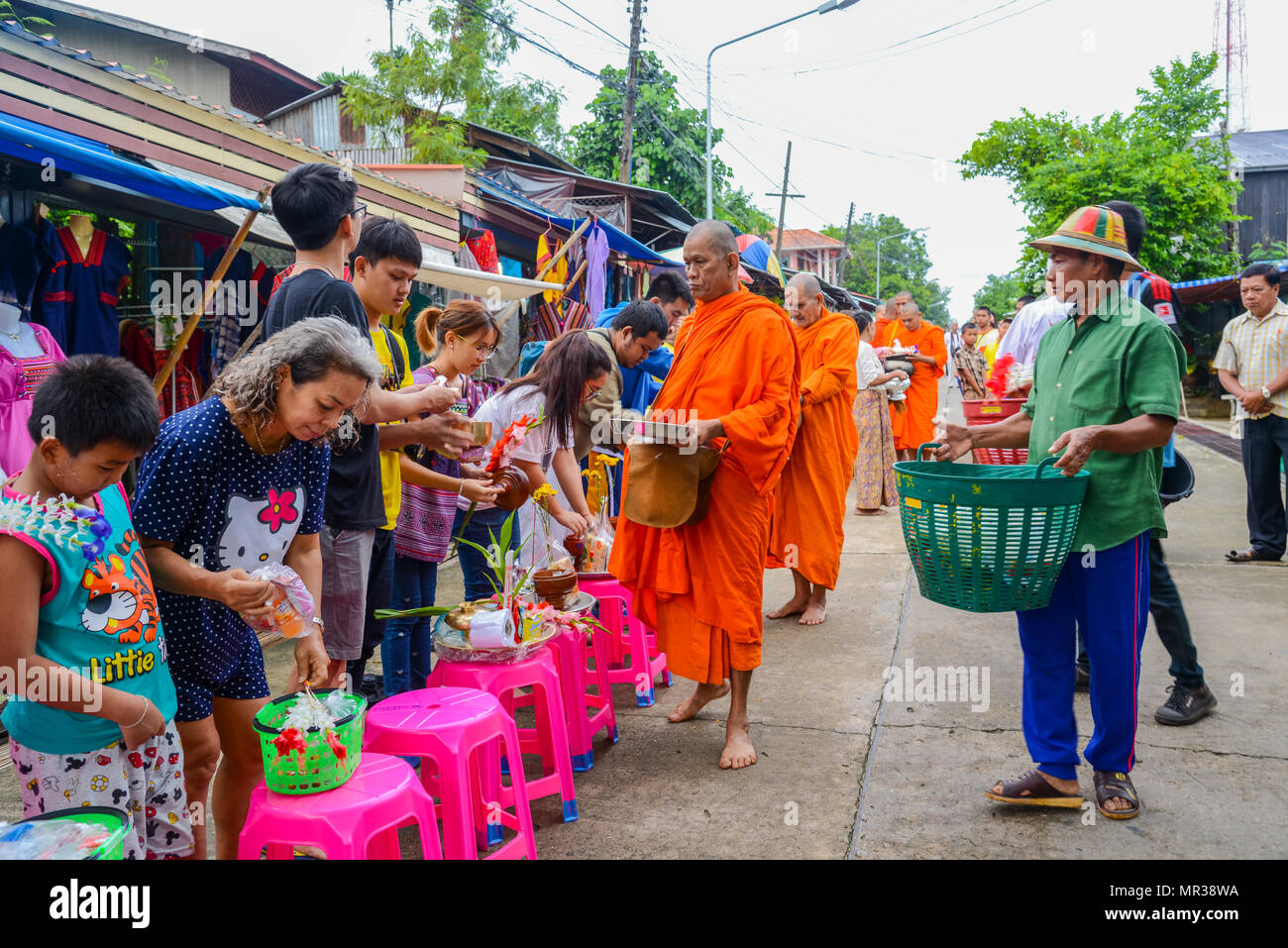 Kanchanaburi, Thailand - July 23, 2016: People offering food and things to group of Buddhist monks in morning on rural street in Kanchanaburi, Thailan - Stock Image