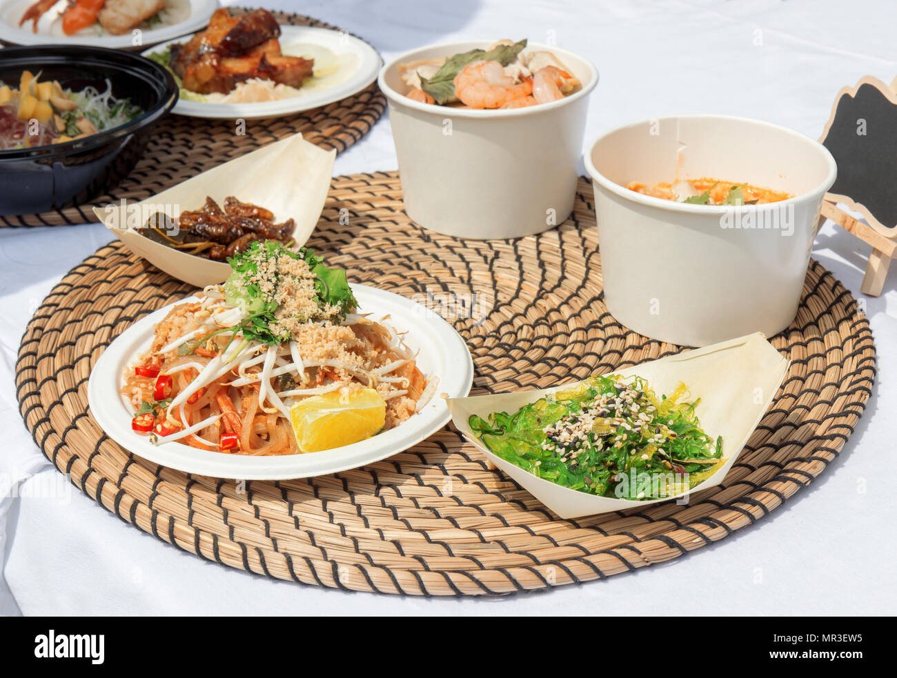 food samples, variations of diverse Asian dishes served on trays during the Asian street farmers market. Soft shell Crab Bao, roasted silkworm, Tom Yu Stock Photo
