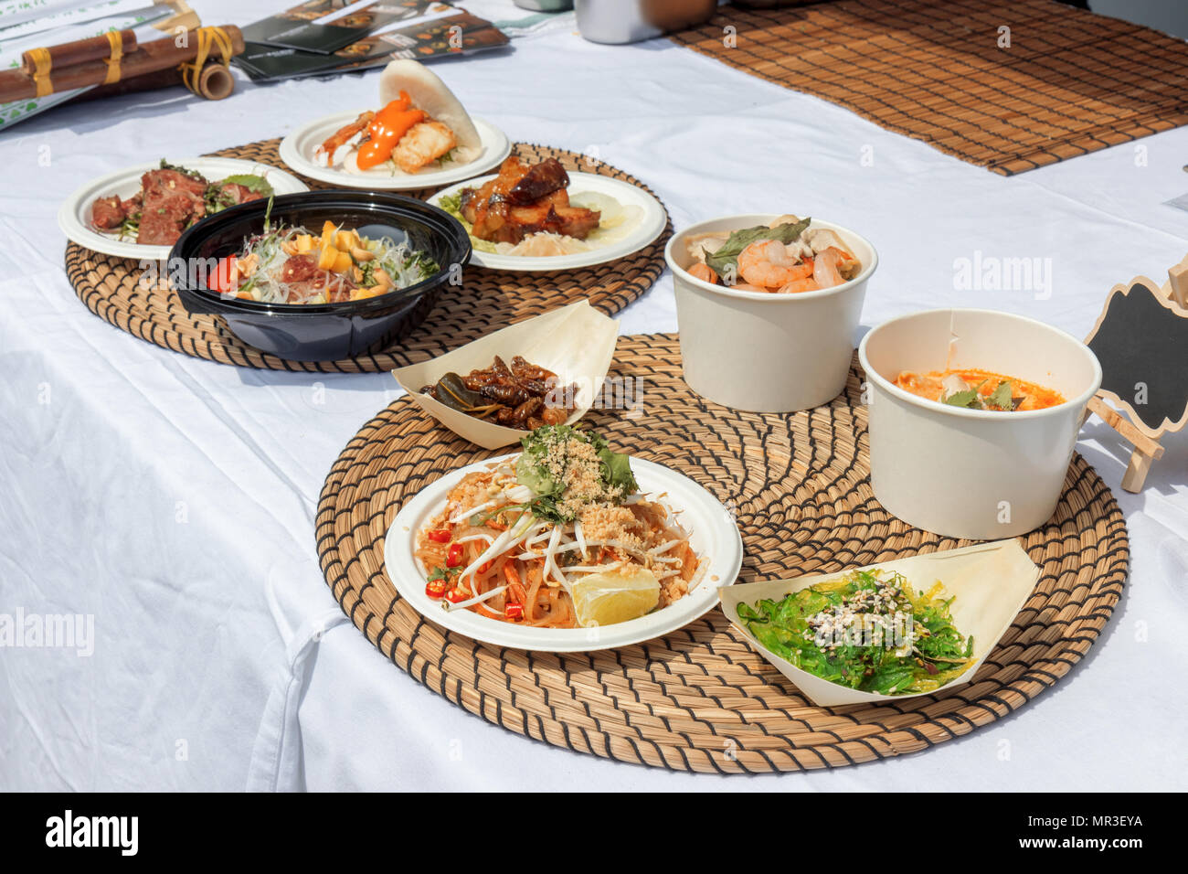 food samples, variations of diverse Asian dishes served on trays during the Asian street farmers market. Soft shell Crab Bao, roasted silkworm, Tom Yu - Stock Image