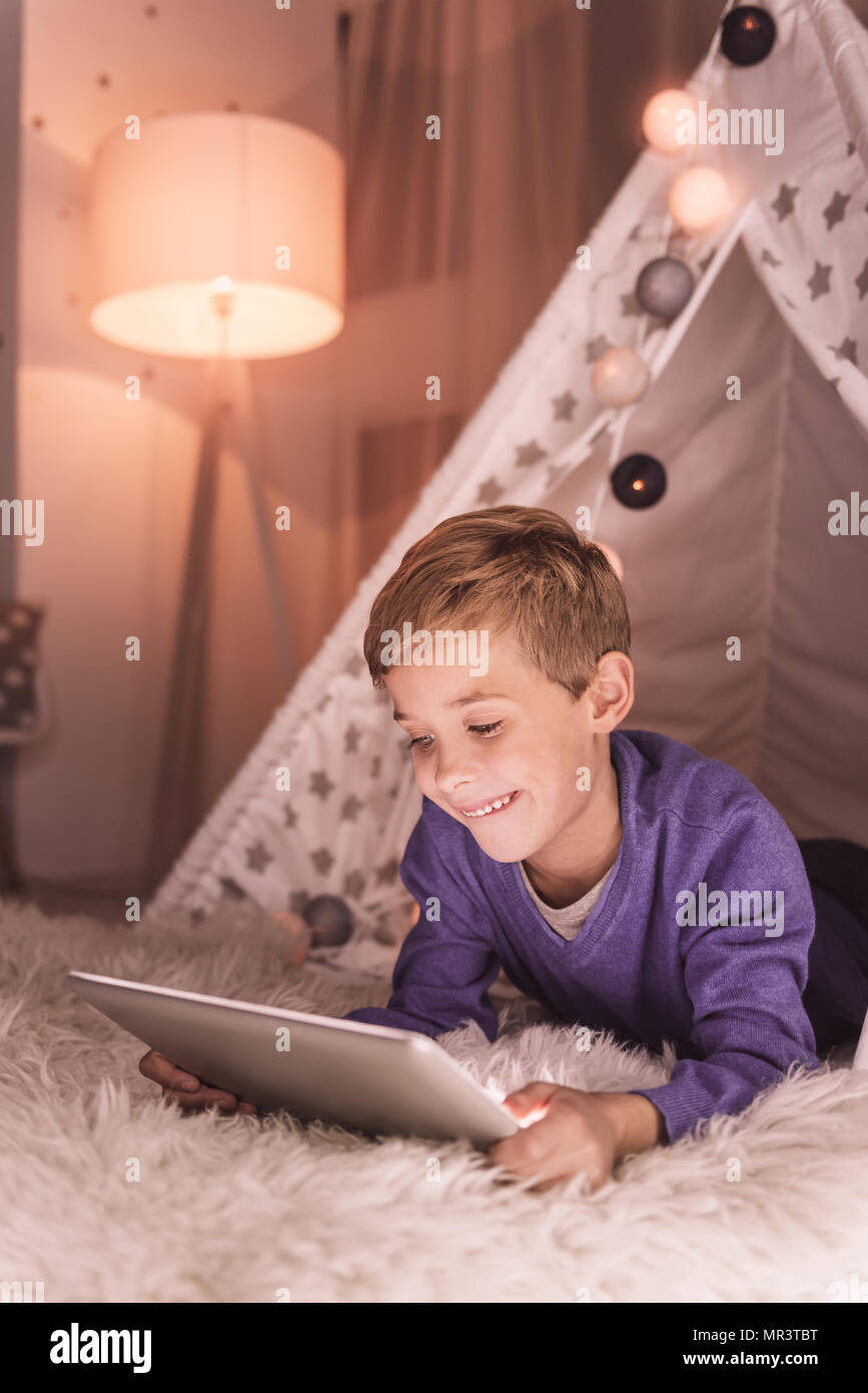 Smart positive boy looking at the tablet screen - Stock Image