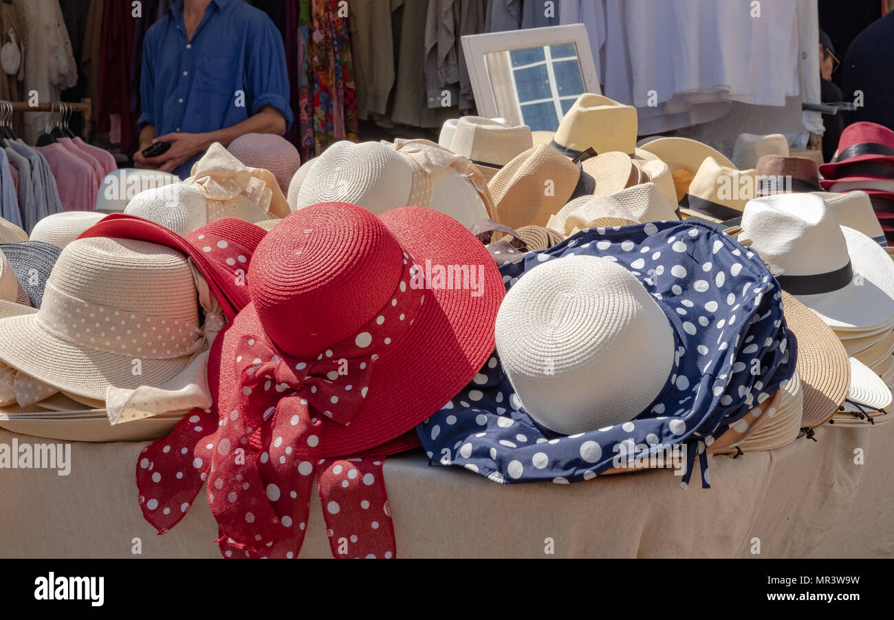 Selection of woman's summer hats together with some men's hats seen at market stall in a famous market. - Stock Image