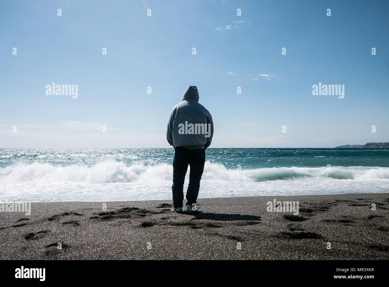 Lone adult male wearing a hooded top contemplating whilst looking at waves and the Salobrena, Southern Spain - Stock Image