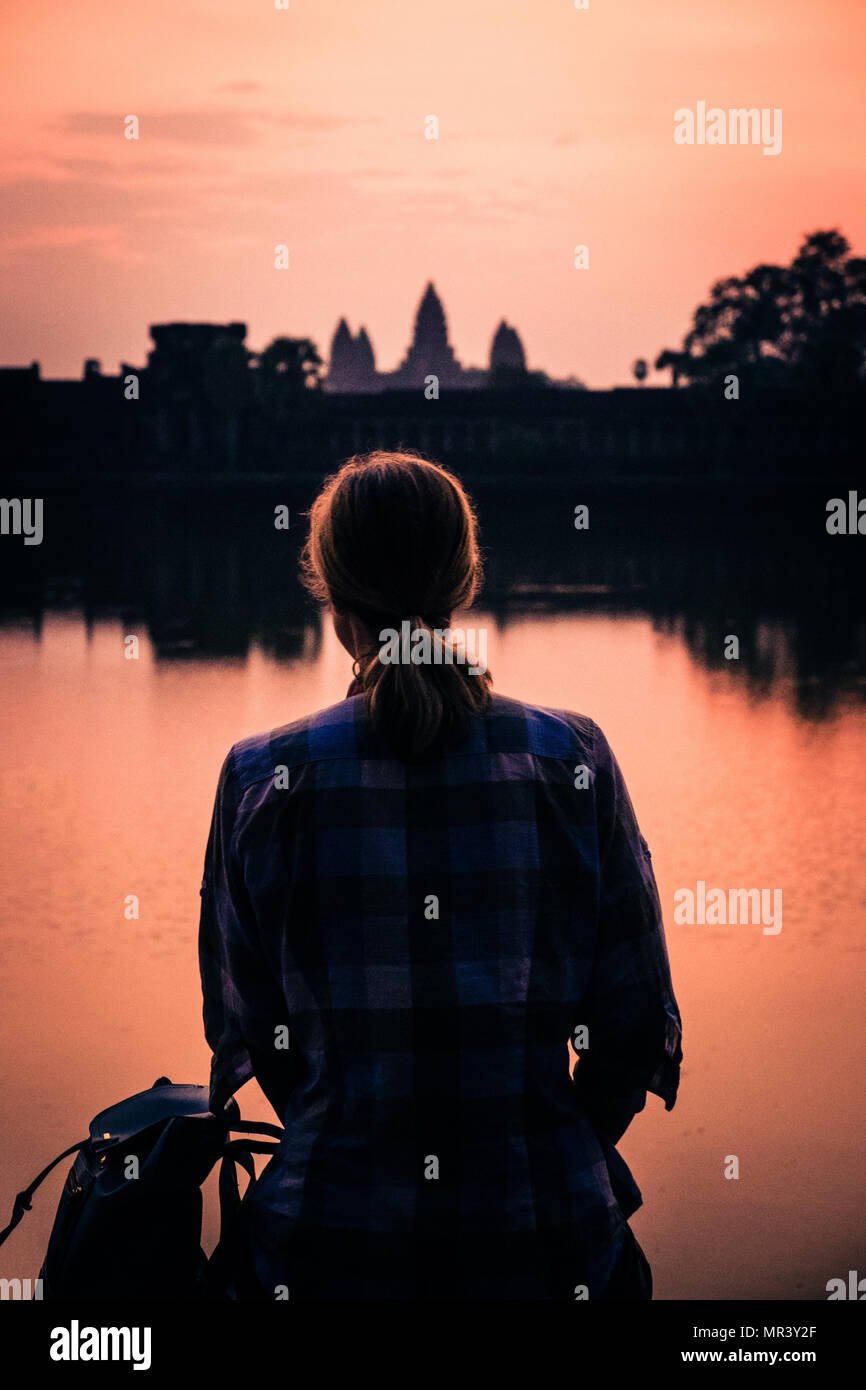 Lone adult female with back to camera watches sunrise reflected across lake at Angkor Wat Temple complex, Angkor, Siem Reap, Cambodia, south East Asia - Stock Image