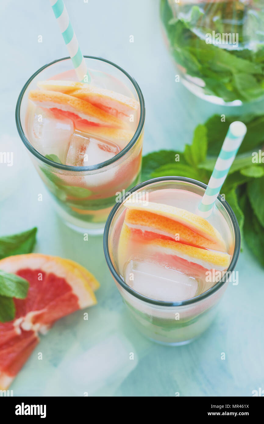 Refreshment grapefruit cocktail with mint on mint color background. Healthy citrus summer drink. Toned - Stock Image