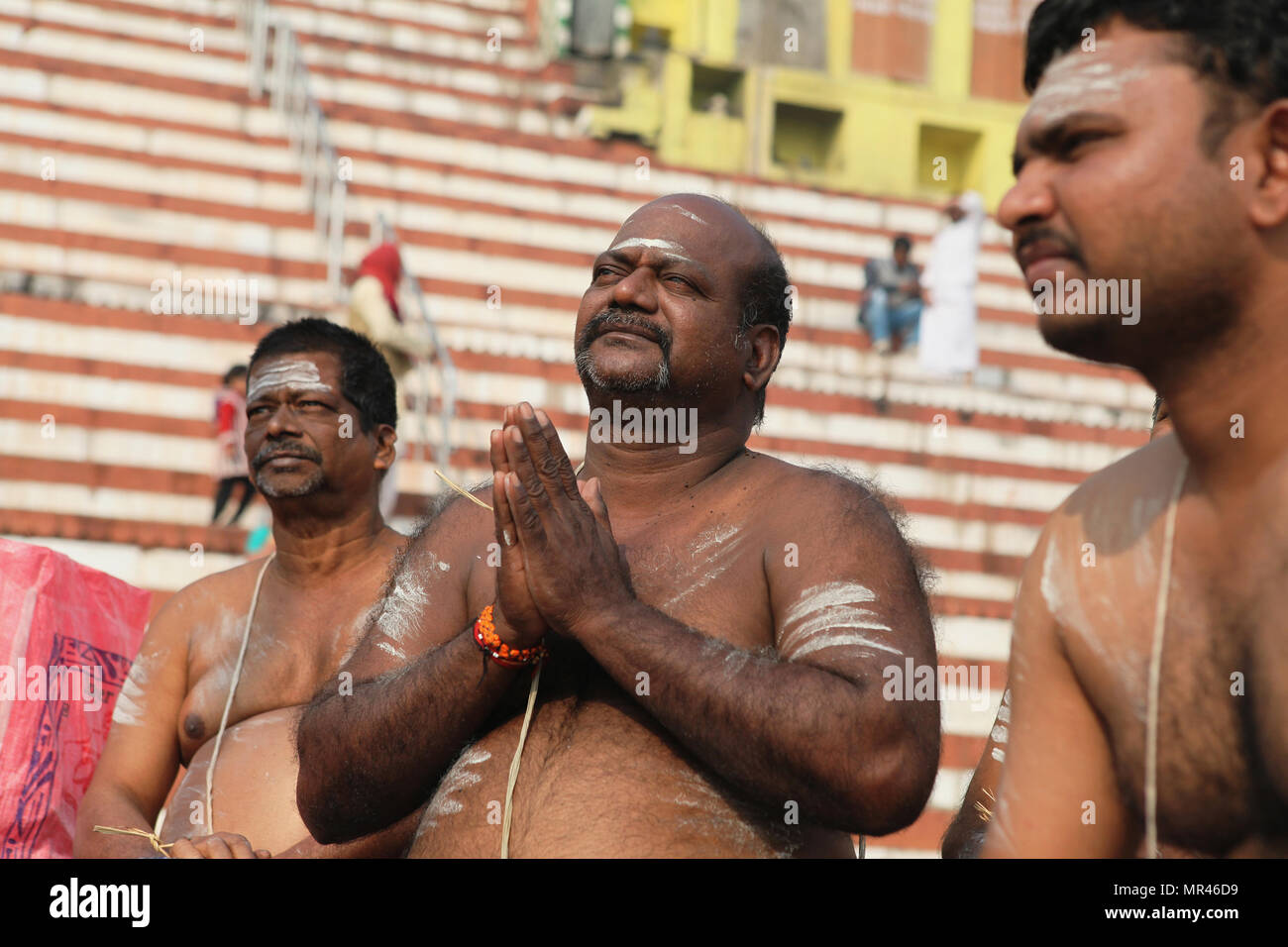 India, Uttar Pradesh, Varanasi, A bereaved man praying at Kedar Ghat. - Stock Image