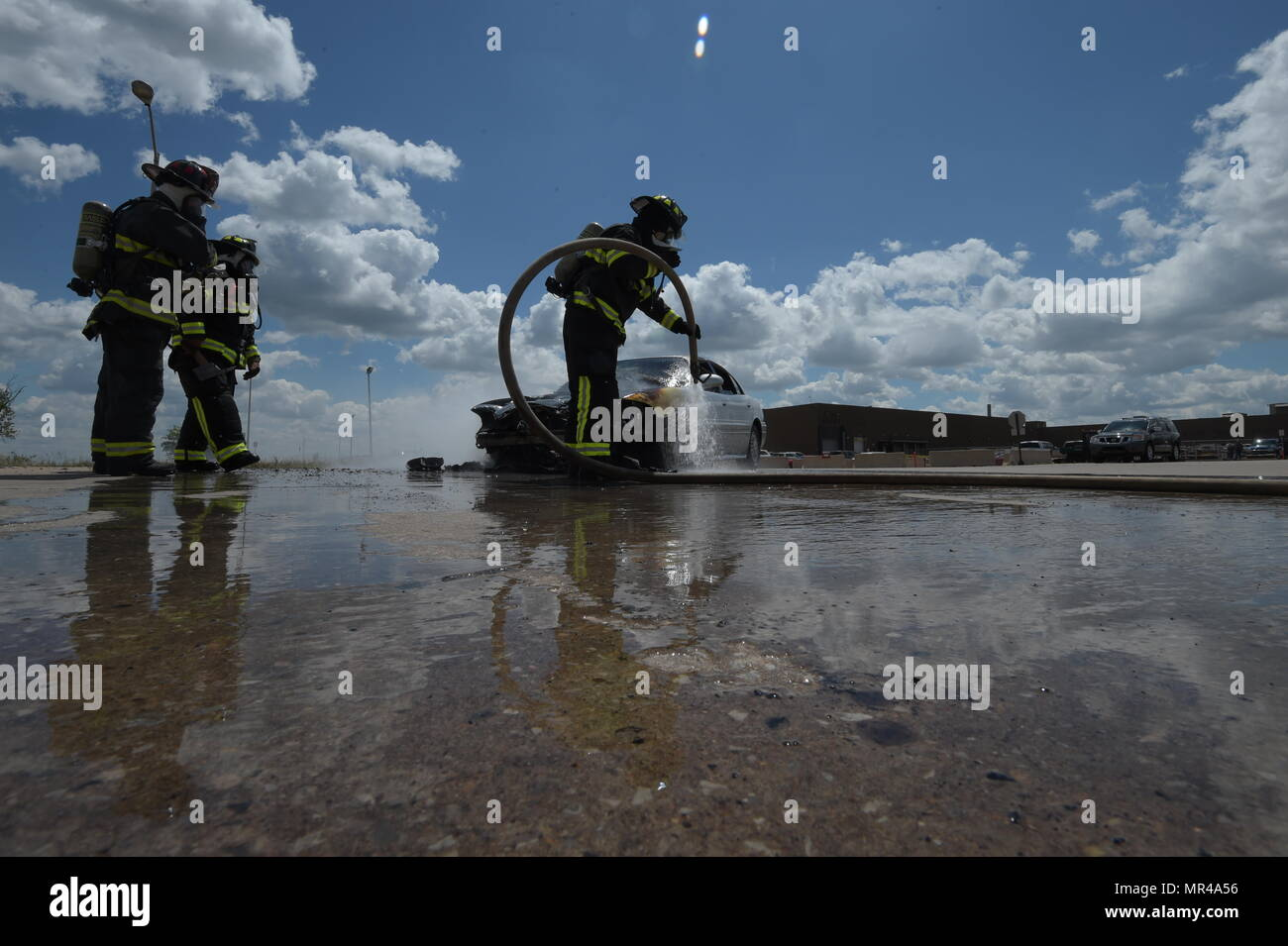 Members of the Tinker Fire and Emergency Services, 72nd Civil Engineer Squadron, work together to extinguish a vehicle fire May 4, 2017, Tinker Air Force Base, Oklahoma. William Green hoses the wheel-well of the car down while Capt. David Jones, left, and Aaron Simpson, background, stands-by as spotters. The privately-owned vehicle developed mechanical trouble and caught fire near the Oklahoma City Air Logistics Complexs' building 9001. (U.S. Air Force photo/Greg L. Davis) - Stock Image