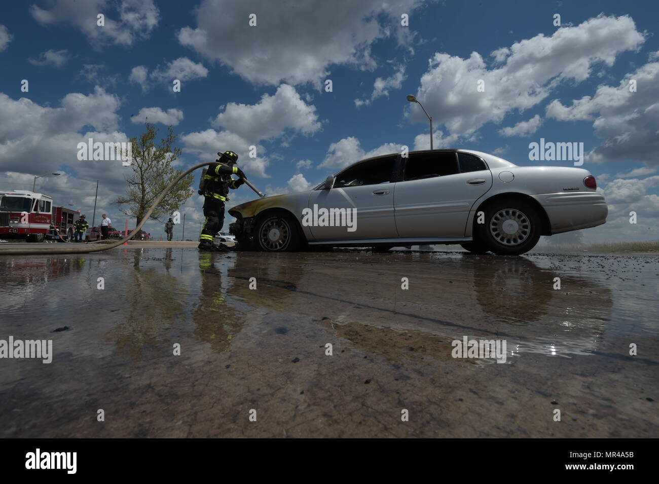 William Green, Tinker Fire and Emergency Services firefighter, sprays water inside the engine compartment while working to extinguish a fire May 4, 2017, Tinker Air Force Base, Oklahoma. The privately-owned vehicle developed mechanical trouble and caught fire near the Oklahoma City Air Logistics Complexs' building 9001. The fire was quickly and safely extinguished by Tinker Fire and Emergency Services, a division of the 72nd Civil Engineer Squadron. (U.S. Air Force photo/Greg L. Davis) - Stock Image