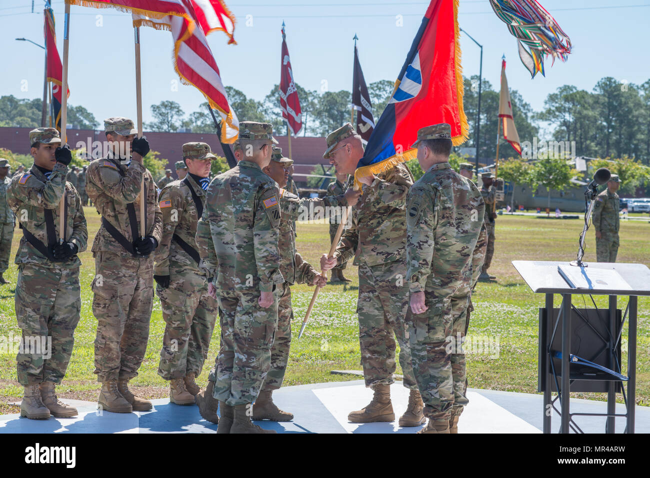 Command Sgt. Maj. Walter Tagalicud, left, 3rd Infantry Division command sergeant major, passes the division colors to outgoing commander, Maj. Gen. James Rainey. The 3rd Infantry Division change of command ceremony was held on Cotrell Field at Fort Stewart, GA, May 8, 2017. Maj. Gen. Leopoldo Quintas assumed command. (U.S. Army Photo by Lt. Col. Brian J. Fickel) - Stock Image