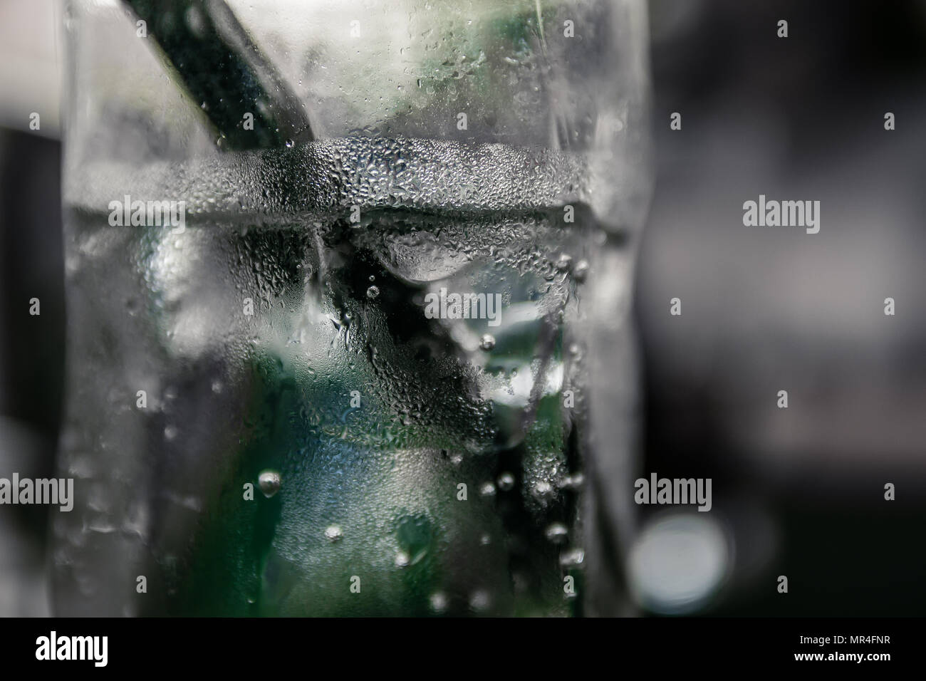 Close up of glass with sparkling water in it. There is a black straw inside the glass. Blurred green bottle behind the glass. - Stock Image