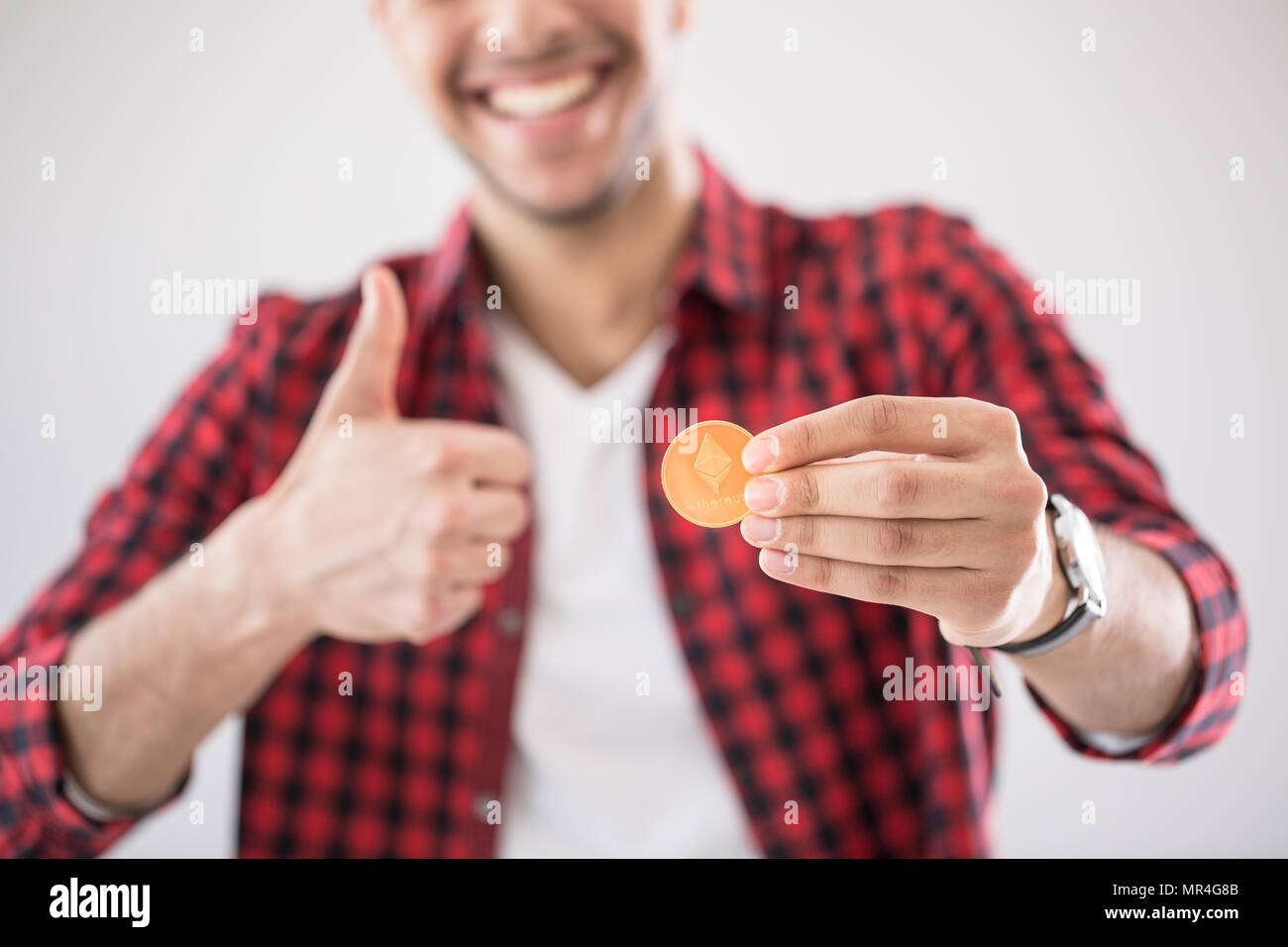 Happy investor with gold cryptocurrency coin - digital money concept - Stock Image