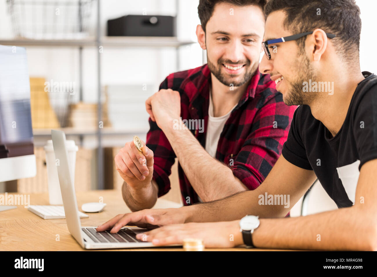 Stockbrokers buying cryptocurrency using laptop - virtual money on the Internet - Stock Image
