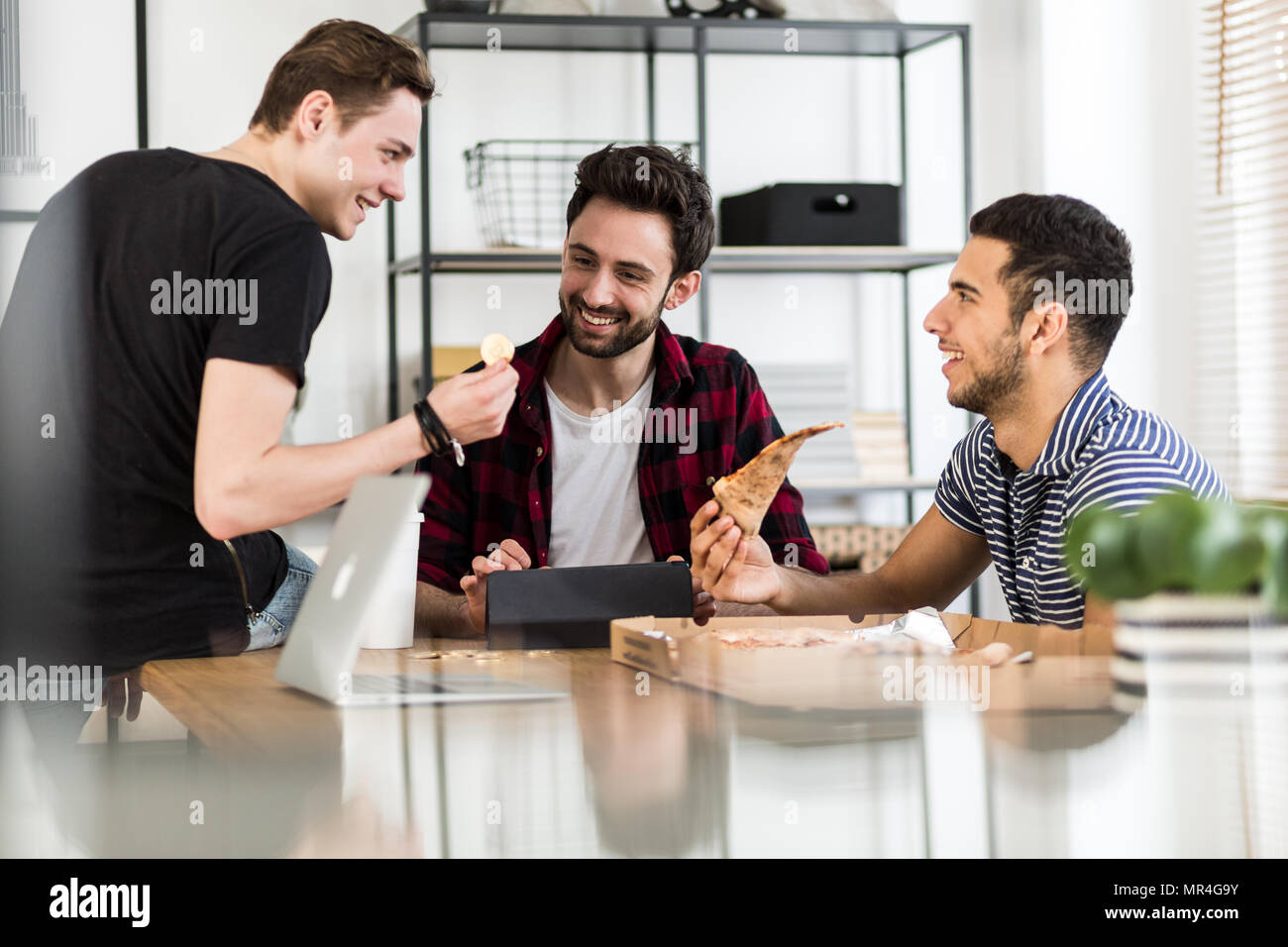 Smiling friends eating pizza and talking about digital cryptocurrency - Stock Image