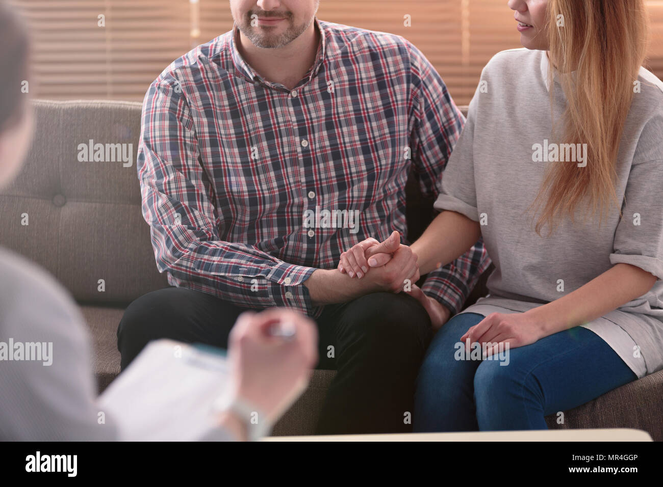 Close-up of woman and man holding hands on a couch during a psychotherapy session. Couples therapy concept - Stock Image