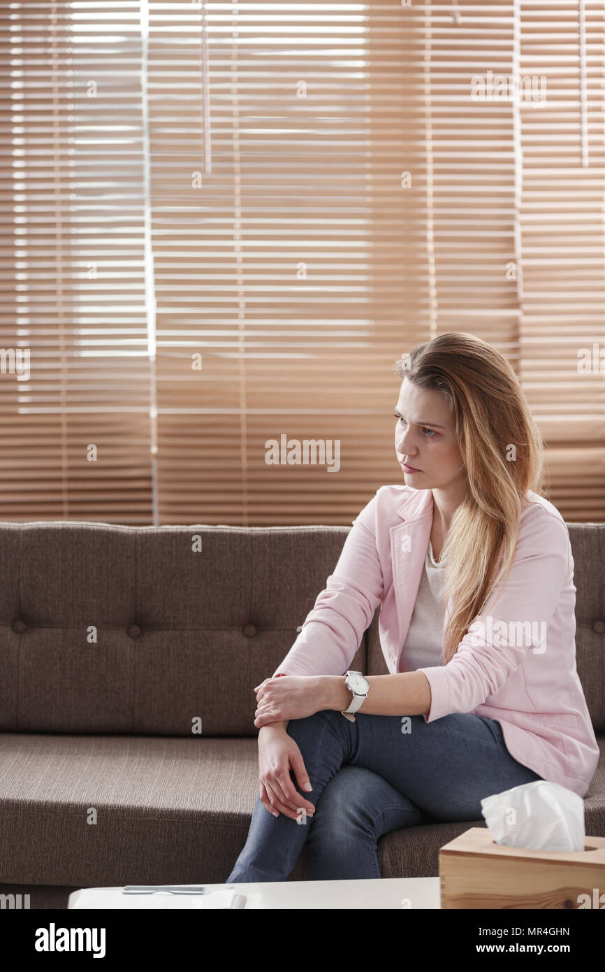 Young woman with depression sitting alone on a couch with a tissue box in front of her during a therapy session - Stock Image