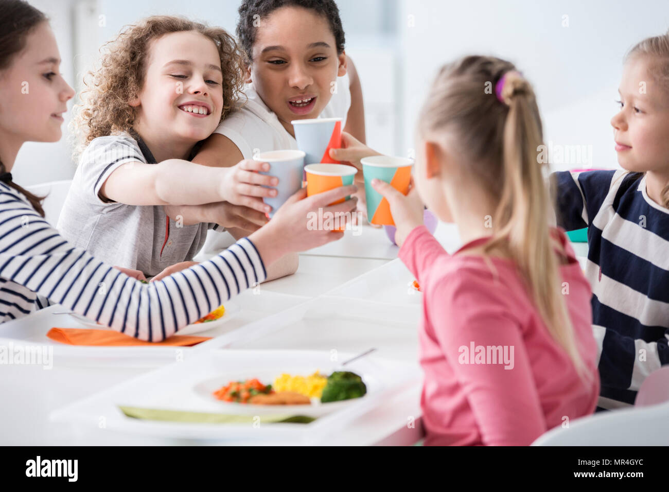 Multicultural group of children toasting during birthday party at home - Stock Image