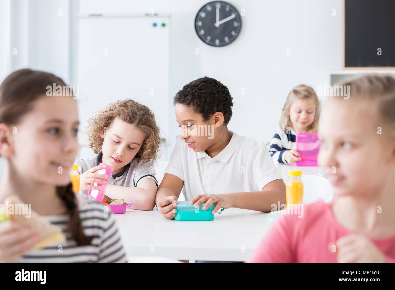 African-american boy eating lunch with friend in the school's canteen Stock Photo