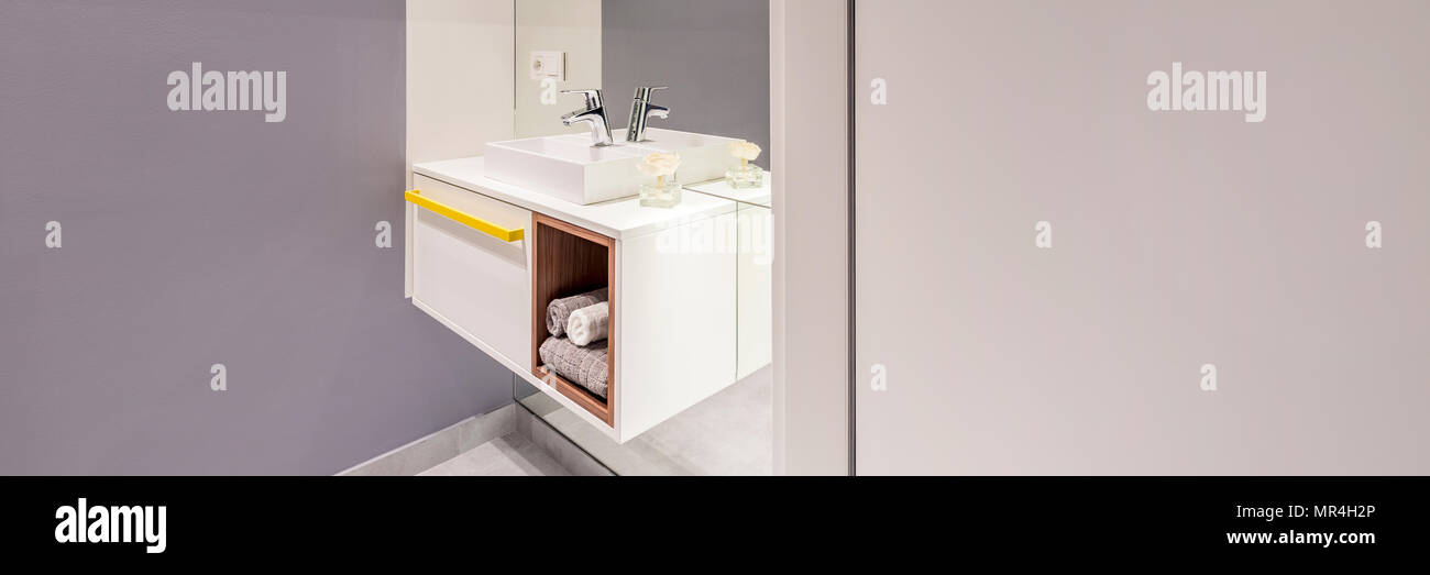 Side View Of Modern Washbasin With A Cabinet And Towels Next To An Empty  Wall In Bathroom Interior